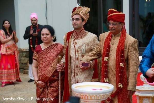 Indian groom escorted by bridals parents.