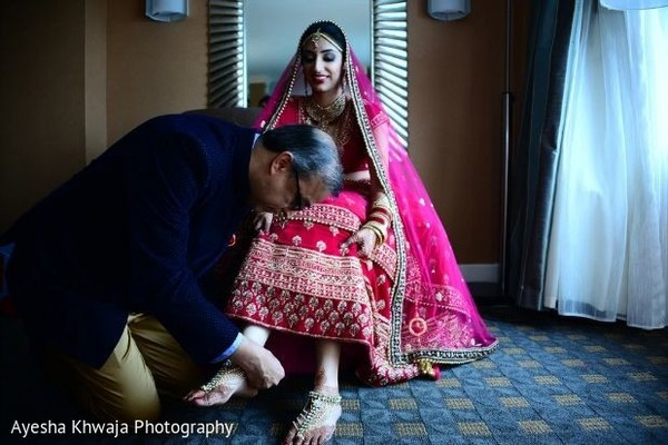 Indian bridals father puttin on her kundan anklets.