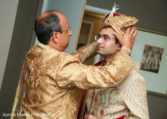 Indian groom getting on his golden and red turban.