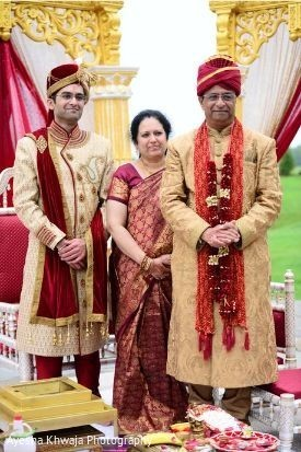 Indian groom waiting for bride with relatives at mandap.