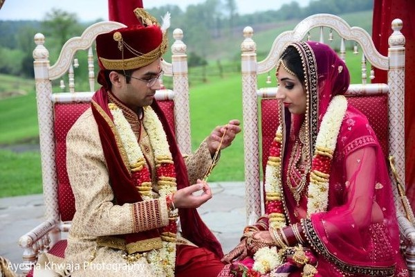 Indian groom putting the mangalsutra necklace.