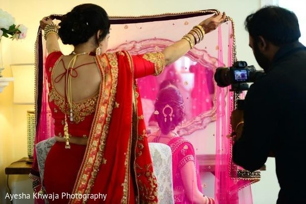 Indian bride's mother putting her ghoonghat on.