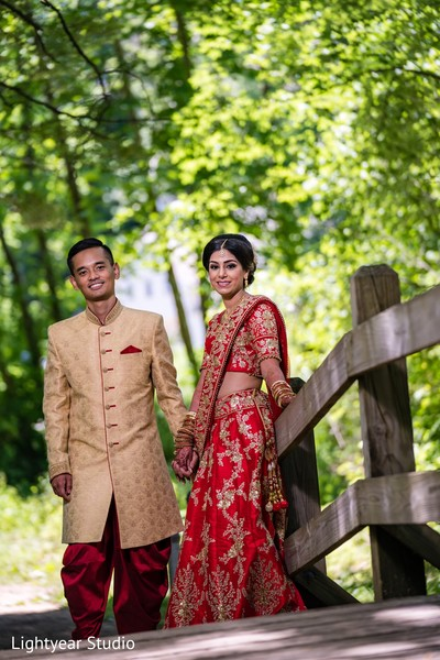 Indian couple in wedding attires posing for picture.