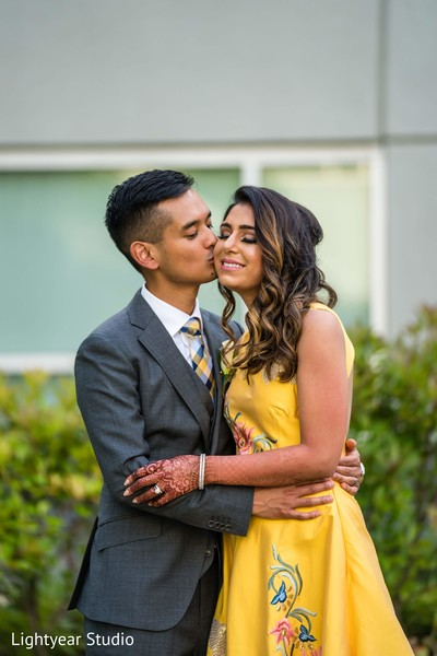 Indian groom in grey suit kissing his Maharani in yellow dress.