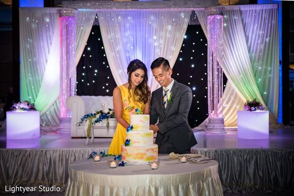 Indian couple cutting wedding cake.