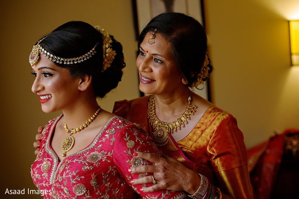 Indian bride with mother on their ceremony hairstyle.