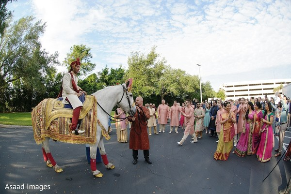 Indian groom on his white horse at his baraat procession.