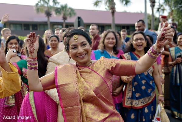 Indian wedding guest on her golden and magenta saree.