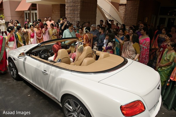 Indian couple leaving ceremony on their white vehicle.