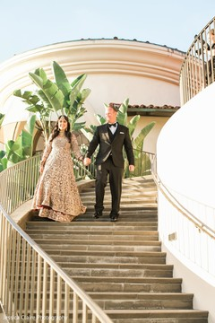 Elegant Indian couple walking down the stairs.