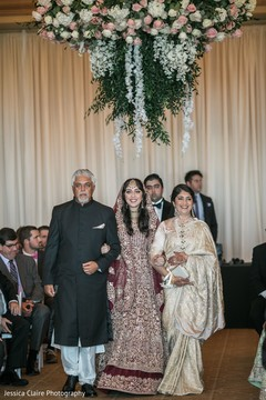 Gorgeous Indian bride escorted down the aisle by her parents.