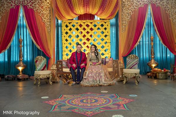 Enchanting Indian couple posing at Sangeet stage.