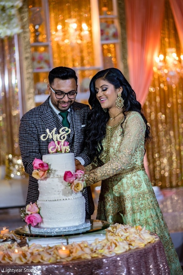 Indian newlyweds cutting the cake during the reception.
