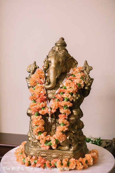 Statue of Ganesha decorated with a peach flower garland.