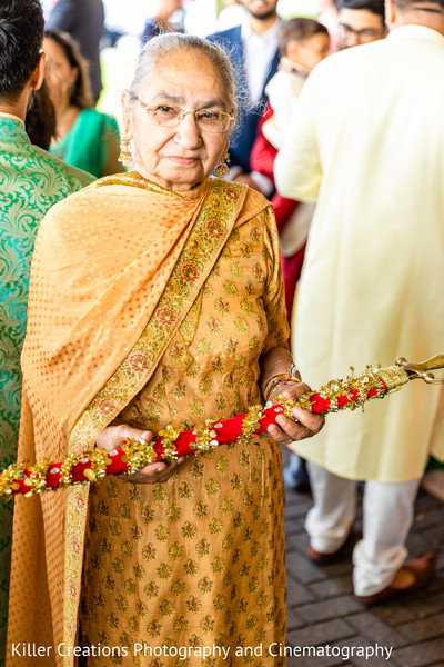 Indian relative holding Indian's groom cane.