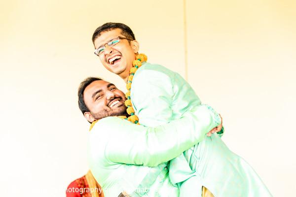 Indian groomsmen hugging.