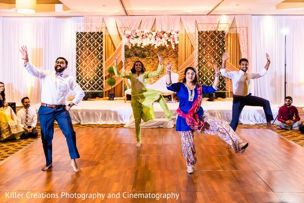 Indian groomsmen and Indian bridesmaids in dancing performance.