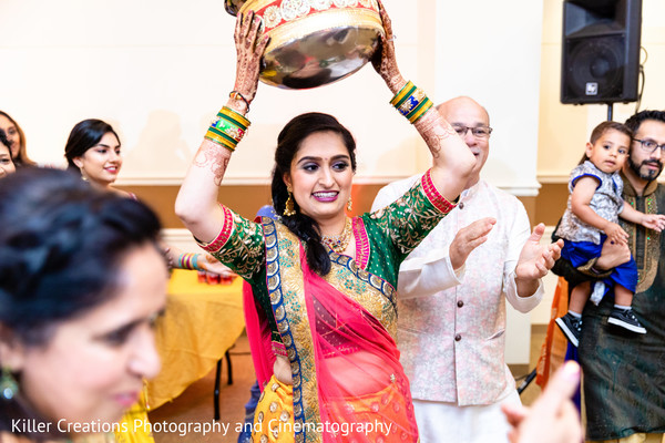Indian bride lifting a basket during the sangeet.