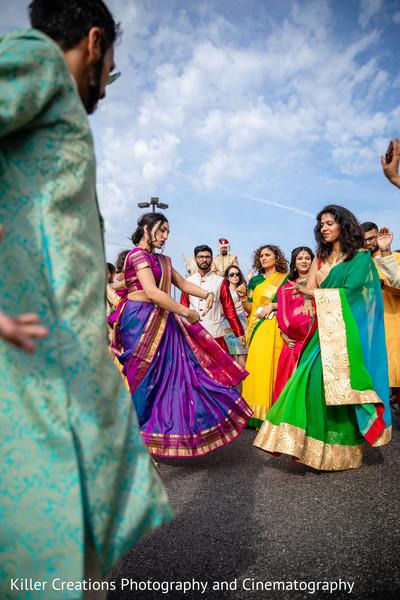Indian bridesmaids dancing during the baraat parade.