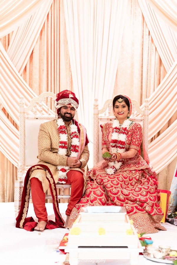 Indian groom wearing a turban and Maharani with a red lengha.