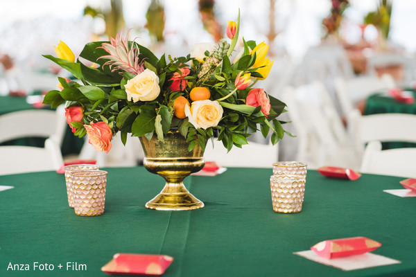 Indian wedding table roses and tropical flowers decoration.