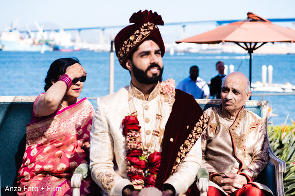 Indian groom and relatives waiting for bride at mandap.