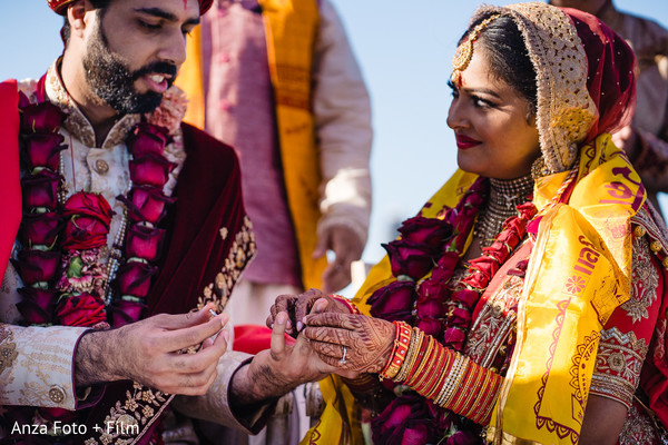 Indian bride putting ring to groom during the wedding ceremony.