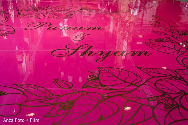 Magenta and golden Indian wedding dance floor decoration.