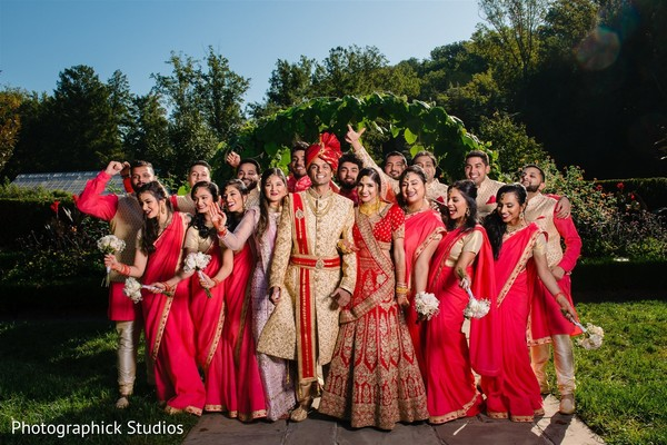 Indian couple posing with groomsmen and bridesmaids outdoors.