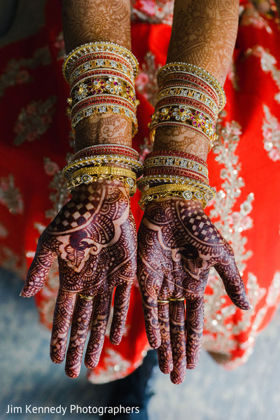 Indian bride showing her palms filled with mehdni art.