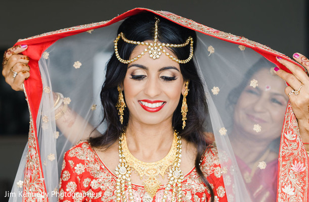 Indian bride being assisted by an Indian relative.
