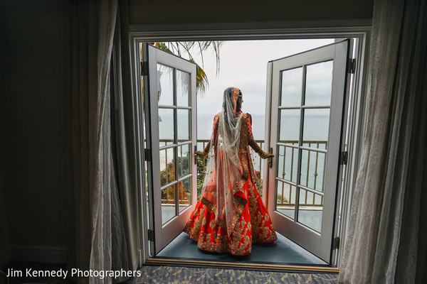 Indian bride with hindu wedding outfit by the window.