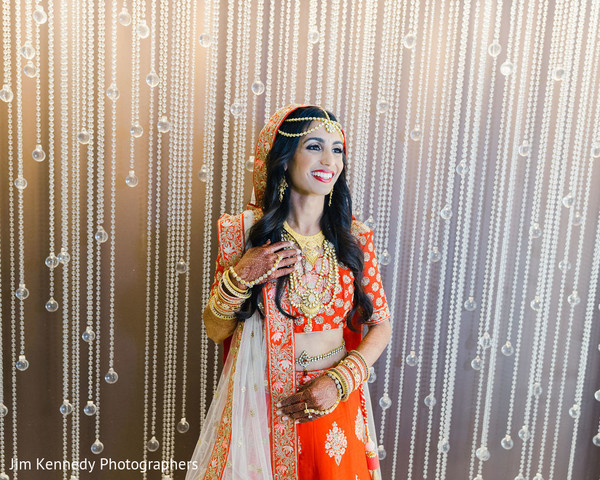 Indian bride with red lengha and golden jewelry.
