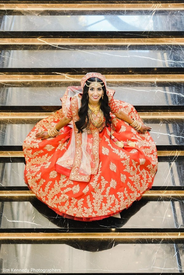 Maharani showing a red lengha during photo shoot.