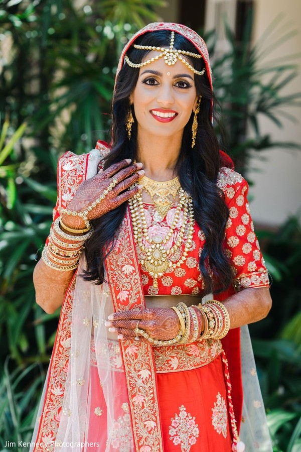 Maharani showing a red lengha with golden details.