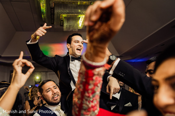 Indian groom lifted by groomsmen at reception party.