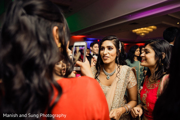 Indian bride sharing with bridesmaids at reception party.