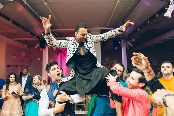 Indian groom being lifted by groomsmen during the celebrations.