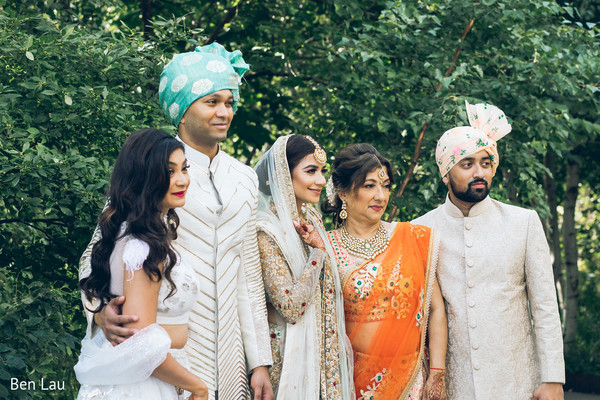 Indian newlyweds posing with special guests outdoors.