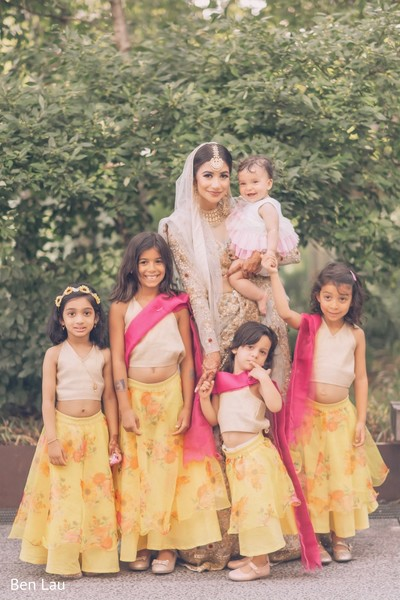 Indian bride posing with lovely kid guests during the photo shoot.
