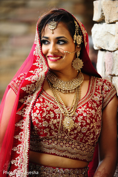 Indian bride showing golden jewelry.