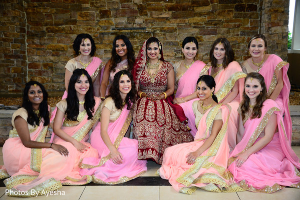 Maharani in red anarkali surrounded by her Indian bridesmaids.