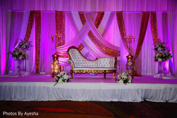 Stage decorated with flowers for Hindu wedding reception.