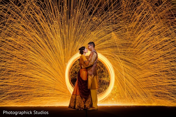 Indian couple posing next to fireworks.