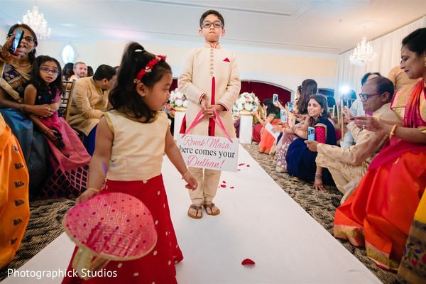 Lovely Indian pageboy holding a white and pink sign at ceremony.