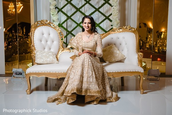 Indian bride sitting on her golden and cream white reception seat.