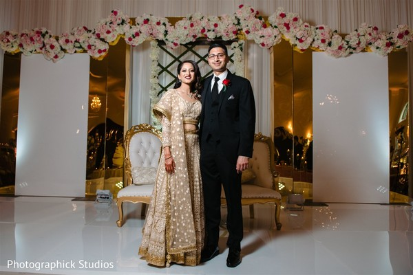 Indian couple posing at white and golden reception stage.