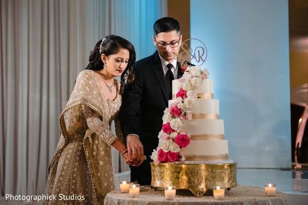 Indian couple cutting white and rose gold wedding cake.