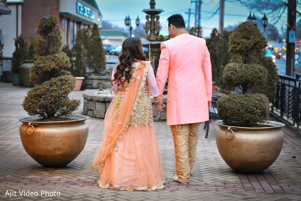 Indian bride and groom walking outdoors on their engagement outfits.