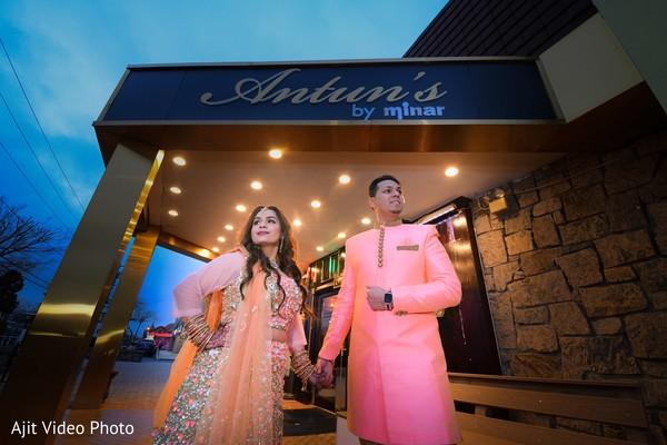 Indian lovebirds posing at engagement venue entrance.